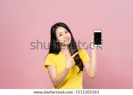 Portrait of Asian beautiful young woman holding smartphone and pointing finger on mobile phone with smile face. The girl standing and looking at camera in studio. Advertisement & presentation concept. #1511205563