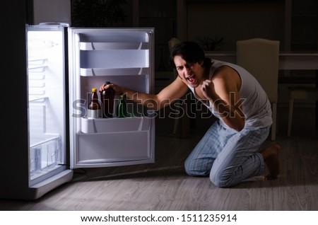 Man breaking diet at night near fridge #1511235914