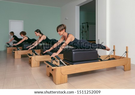 Seregno-Italy 07-17-2019 four women perform pilates exercises in the gym with the help of a bench to keep fit #1511252009