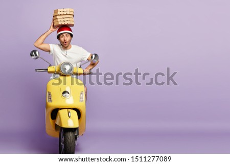 Pizza delivery courier carries stack of carton boxes over head, wears protective helmet and white t shirt, rides on yellow motorbike, poses against purple background, blank space. Food transportation #1511277089