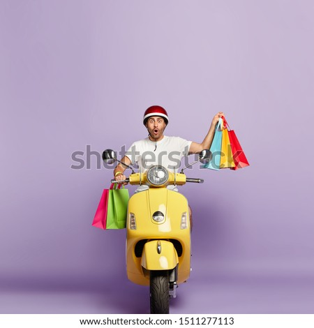 Vertical image of impressed handsome guy in casual wear, returns from shop, carries shopping bags, shocked, drives on fast motorbike, works as courier, isolated over purple background. Purchasing #1511277113