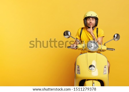 Surprised young man with European appearance makes silence gesture, touches index finger over lips, tells secret, wears yellow helmet and casual t shirt has own transport poses indoor. Male on scooter #1511279378