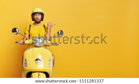 Horizontal shot of man has stubble points away with thumb, shows direction on right side, wears protective headgear and moped, isolated over yellow background. People, transportation concept #1511281337
