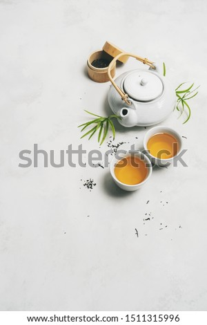 Asian tea concept with Tea set surrounded with dry green tea on white background with space for text. Brewing and Drinking tea. #1511315996
