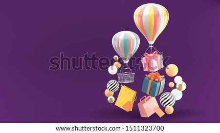 Balloon, gift box and shopping bag surrounded by colorful balls on a purple background.