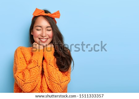 Portrait of cheerful mixed race woman has shy satisfied expression, smiles broadly, shows white teeth, wears orange bow headband and knitted sweater, poses against blue background. Ethnicity, emotions #1511333357