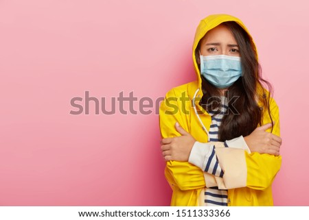 Upset Asian woman trembles from cold, has virus transmitted through airbone droplets, wears protective medical mask, yellow raincoat with hood, stands against pink wall, has contagious disease Royalty-Free Stock Photo #1511333366