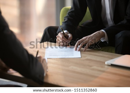 Close up businessmen signing partnership agreement, business partners making legal deal, putting signature on official paper document, taking loan or purchase property, male hands holding writing pen #1511352860