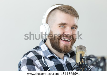Radio and DJ concept - Man with microphone and big headphone is smiling #1511396591