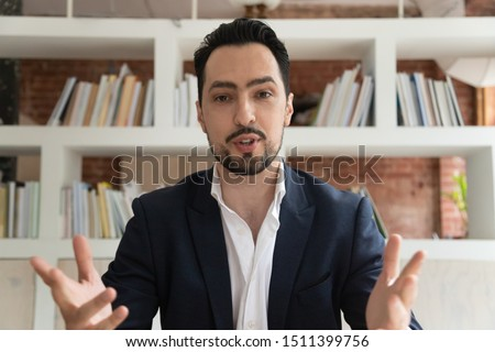 Web cam view of confident middle east appearance businessman having formal conversation talking corporate client look at camera or coach lead online communication make conference video webinar concept Royalty-Free Stock Photo #1511399756