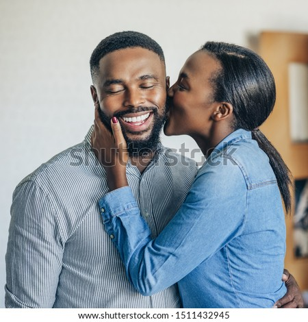 Young African American woman giving her smiling husband a kiss on the cheek in their living room at home #1511432945