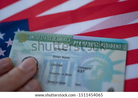 Permanent Resident Green card  of United states of America on flag of USA. Above close up view.  #1511454065