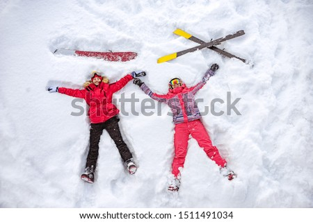 Skier and snowboarder are lying on snow with ski and snowboard and having fun. Aerial photo #1511491034