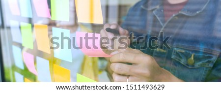 Business people meeting at office and use sticky notes on glass wall in office, diverse employees people group planning work together brainstorm strategy #1511493629