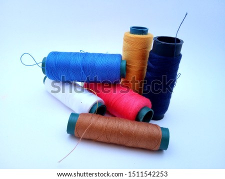 six spools of colorful thread. There are white, brown, pink, blue, yellow, and navy #1511542253