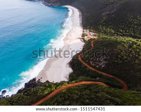 Isolated road down to Shelly Beach, Albany, Western Australia. The windy road takes you down to the isolated Shelly Beach with blue water and cliffs surrounding the beach. Shot aerially on a drone.  #1511547431