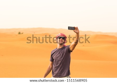 Man taking a selfie on top the desert dunes. Travel and Tourism.