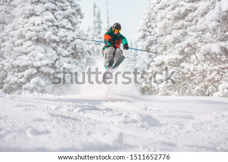 Fast skier freerides and jumps in snowy forest. Offpiste skiing concept #1511652776