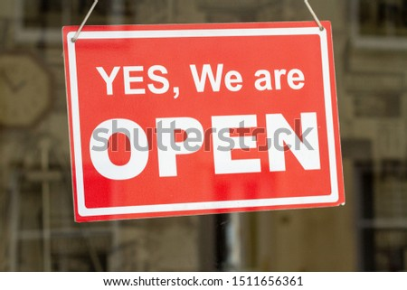 Shop sign with yes, we are open written on it and a reflection #1511656361