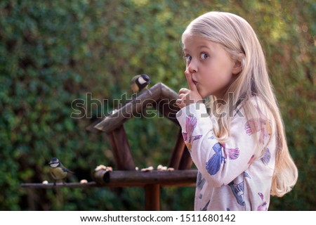 Cute girl watching two birds: a great tit and a blue tit in a bird house feeder while being very quiet. #1511680142