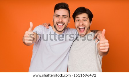 We recommend! Happy men showing thumbs up over orange background #1511696492