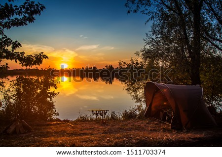 Fishing adventures, carp fishing. Angler, at sunset, is fishing with carpfishing technique. Camping on the shore of the lake.Carp Fishing Sunset Royalty-Free Stock Photo #1511703374