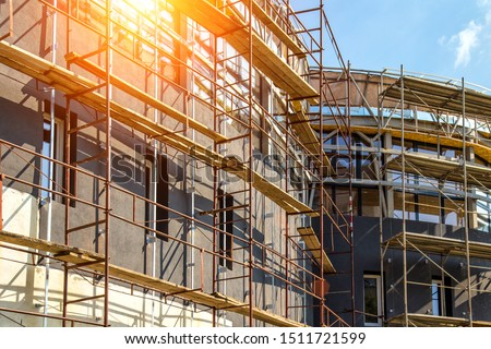 Extensive scaffolding providing platforms for work in progress on a new apartment block,Tall building under construction with scaffolds,Construction Site of New Building #1511721599