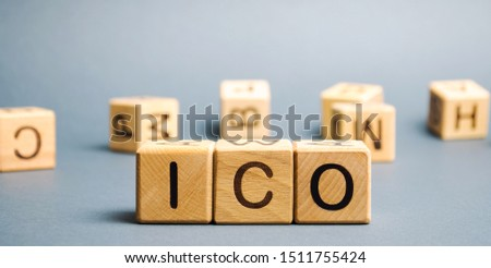 Wooden blocks with the word ICO ( Initial coin offering ). Attracting investments in the form of selling to investors a fixed number of new units of cryptocurrencies #1511755424