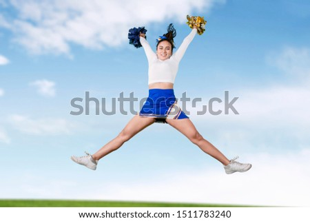 Picture of a beautiful cheerleader girl jumping and doing splits while dancing in the meadow