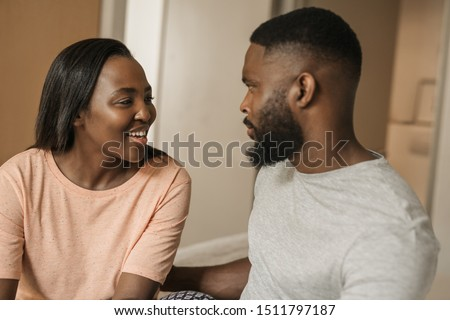 Affectionate young African American couple talking together while sitting in their pajamas on their bed in the morning #1511797187