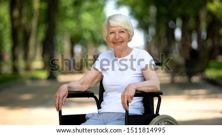 Smiling elderly woman in wheelchair looking into camera, sunny day in park #1511814995