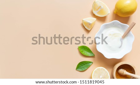 Perfect homemade natural face mask ingredients for bright and healthy skin. Top view of yogurt, lemon and honey on orange background. Beauty herbal skincare product concept. Flat lay. Copy space. #1511819045