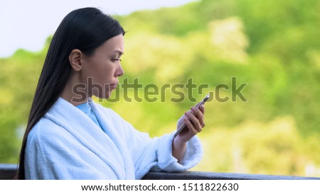 Young woman reading message on smartphone standing hotel balcony outdoors, work #1511822630