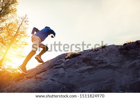 Man runs uphill by big rock against sunset sky #1511824970