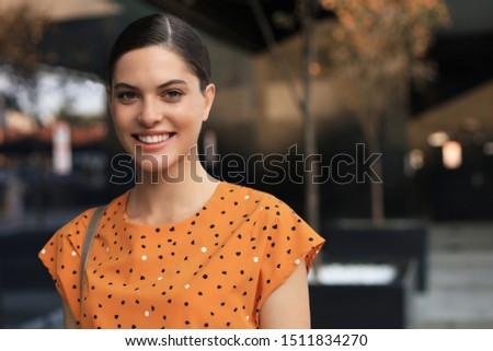 Portrait fashion woman in yellow dress walking on street of the city, smiling at camera #1511834270