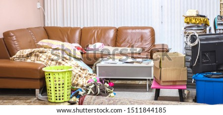 Messy home in living room with cloth, book, toy, box and sofa. Royalty-Free Stock Photo #1511844185