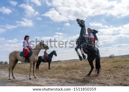 Slavuta, Ukraine - september 22, 2019 : Ukrainian men on horseback participate in the Ethno-eco festival Kolodar in city Slavuta, Ukraine #1511850359