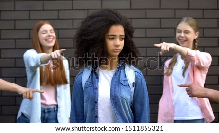Cruel group of teens pointing fingers at curly afro-american schoolgirl, racism Royalty-Free Stock Photo #1511855321