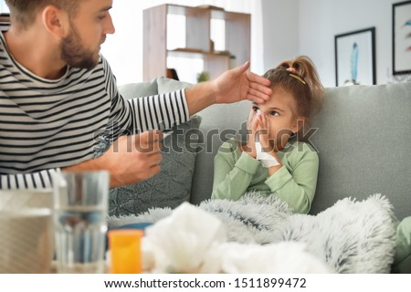 Father taking care of his daughter ill with flu at home Royalty-Free Stock Photo #1511899472