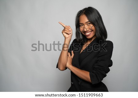 Portrait of attractive young Asian smiling woman in elegant black blazer and glasses pointing index finger up over light gray wall background. Mock up copy space #1511909663