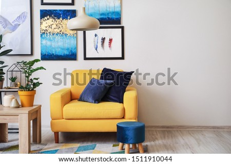 Stylish interior of living room with yellow armchair