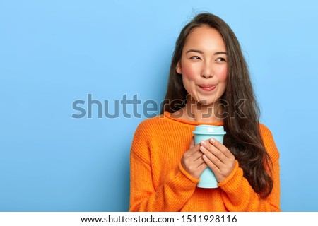 Horizontal shot of dreamy Asian girl licks lips, enjoys taste of aromatic coffee, has long dark hair, wears orange jumper, looks away, poses against blue background. People, drinking, spare time #1511928116