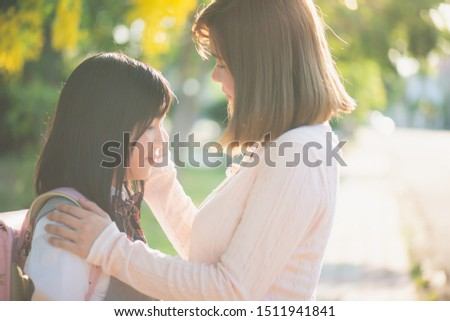 Asian mother saying goodbye to her daughter as she leave for School,back to school concept #1511941841