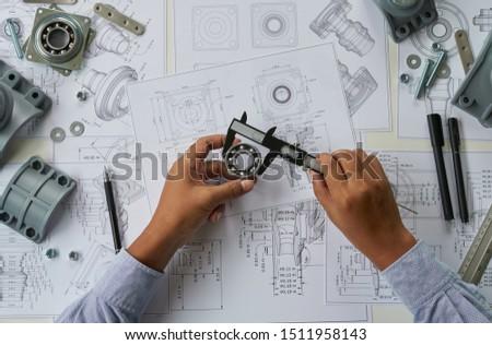 Engineer technician designing drawings mechanicalparts engineering Enginemanufacturing factory Industry Industrial work project blueprints measuring bearings caliper tools #1511958143