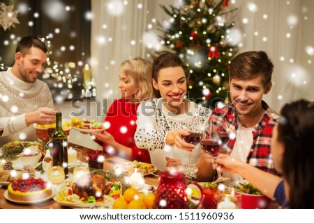 holidays and celebration concept - happy friends having christmas dinner at home, drinking red wine and clinking glasses over snow #1511960936