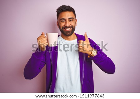 Indian man wearing purple sweatshirt drinking cup of coffee over isolated pink background happy with big smile doing ok sign, thumb up with fingers, excellent sign #1511977643
