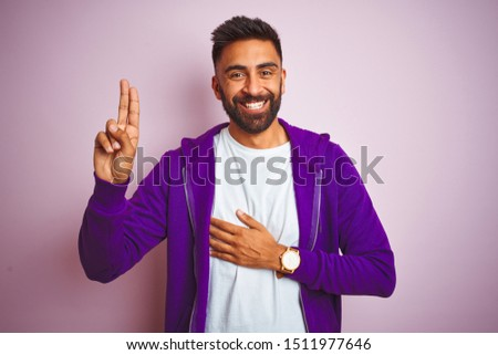 Young indian man wearing purple sweatshirt standing over isolated pink background smiling swearing with hand on chest and fingers up, making a loyalty promise oath #1511977646