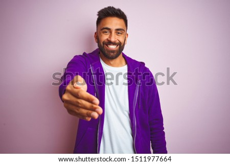 Young indian man wearing purple sweatshirt standing over isolated pink background smiling friendly offering handshake as greeting and welcoming. Successful business. #1511977664