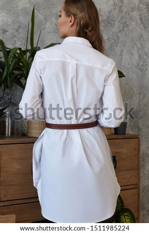 Medium full back shot of a young European lady dressed in a white long-sleeved tunic shirt and a brown belt made of texture leather. The fashion model bronze hairgrips on her long wavy chestnut hair  #1511985224