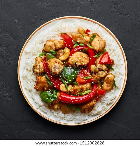 Schezwan Chicken or Dragon Chicken with basmati rice at black slate background. Szechuan Chicken is popular indo-chinese spicy dish with chilli peppers, chicken and vegetables. #1512002828